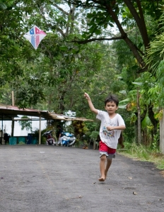 Boy in North Sulawesi flying a kite
