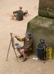 Artist paints while child plays nearby in the sand