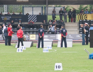 Prince Harry on the far right in black teeshirt and jeans about to present medals