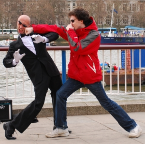 Street performer with a member of the public in red jacket