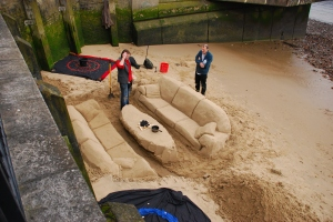 Sand sculpture of sofas and coffee table on the beach by the Thames